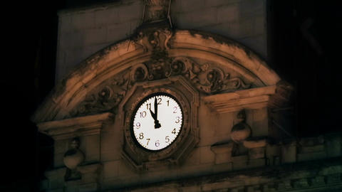 Ancient template clock showing time on old sophisticated building at night Footage