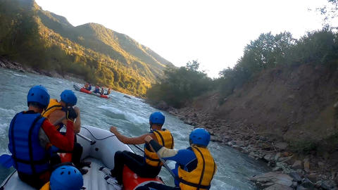 Teams paddling boats along wild mountain river, dangerous white water rafting Footage