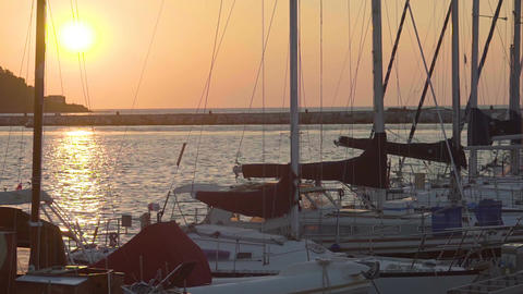 Luxury yachts docked at marine, beautiful seascape, romantic sunset on horizon Footage