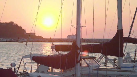 Beautiful sunset view from seaside city, boats at dock, cruise ship on horizon Footage