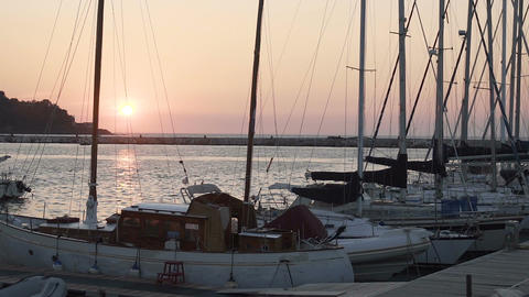 Boats for sale or rent docked at marina, beautiful sunset on horizon, seascape Footage