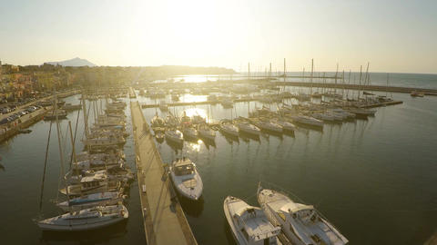 Sunlit sailing boats and yachts docked at marina, mediterranean tourist city Footage