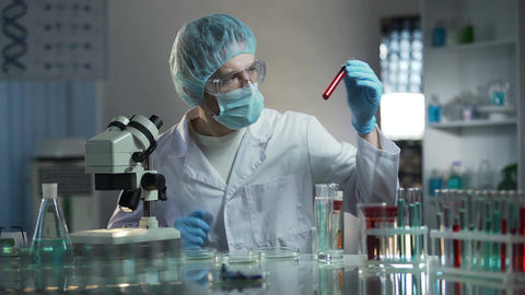 Laboratory worker studying blood samples to detect pathologies, medical research Footage