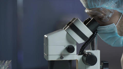 Neurosurgeon carrying out surgery on brain, looking in microscope, microsurgery Footage