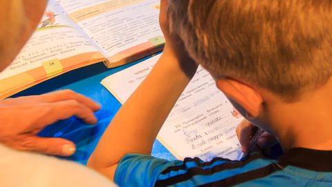 closeup backside woman teaches boy write in ABC work book Footage