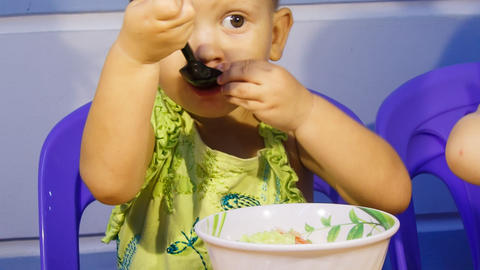closeup little blonde girl eats soup out of bowl Footage