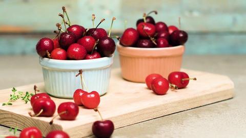 Red ripe cherries in ceramic bowls Footage