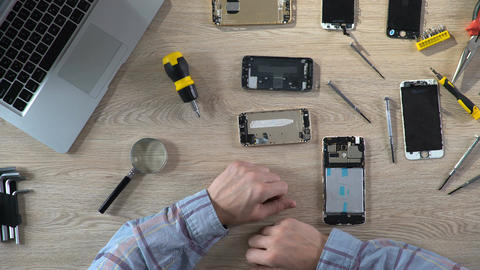 Man repairing broken gadget, diagnosing mobile phone problems, service center Footage