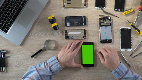 Repairer checking phone functionality after fixing, smartphone with green screen Footage