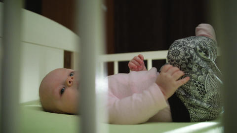 Close up of Infant Baby Laying in Crib Legs Up Motion Footage