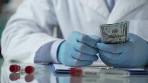 Medical worker counting dollar bills, reward for illegal virus development Footage