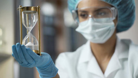 Laboratory worker with hourglass on palm looking at camera after last sand falls Footage