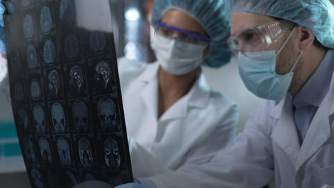 Medical workers looking at human brain MRI, discussing result to set diagnosis Footage