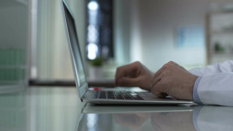 Medical researcher taking test tube from table, typing information on laptop Footage