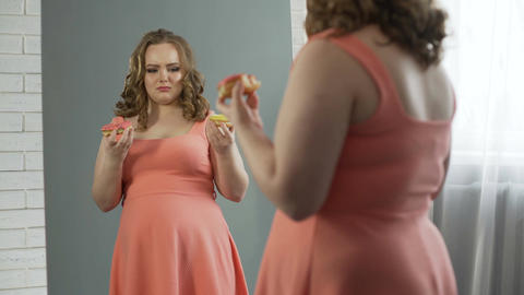 Depressed overweight lady chewing donuts in front of mirror, eating disorder Footage