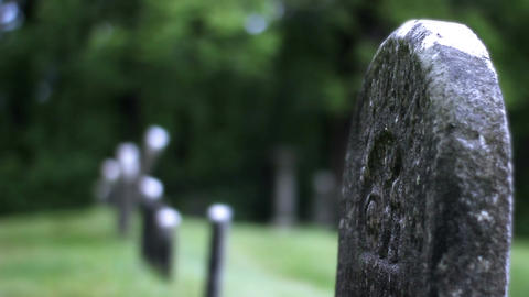 Single lonely tombstone in dreary wet rainy cemetery Footage