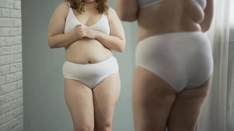 Sad girl embarrassed about her cellulite body and excess weight, health problem Footage