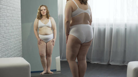 Woman suffering digestive disorders, looking at her fat body, obesity problem Footage