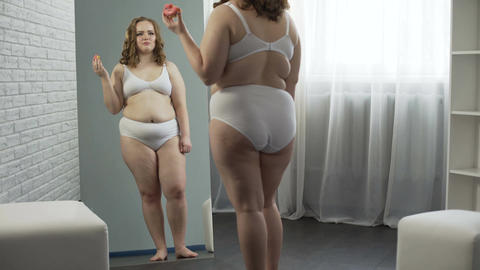 Obese girl hopeless trying to lose weight, crying and eating donut, overweight Footage