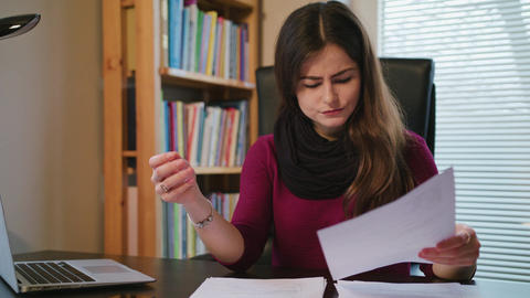 Overwhelmed woman with documents and laptop in home Footage