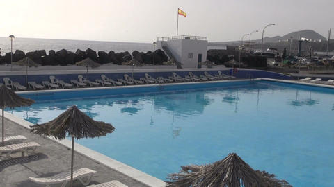 Beach umbrellas and swimming pool in Spain Live Action