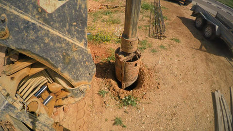 Tractor with a drilling device at a construction site