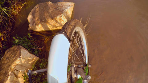 Cyclist crossing a muddy stream with bicycle Footage