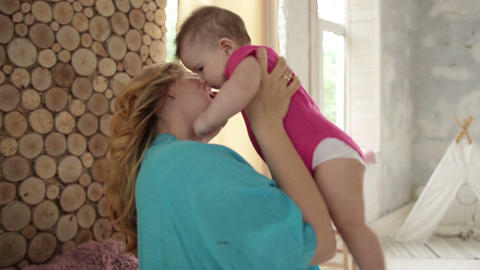 Caring mom kissing her adorable baby girl Footage