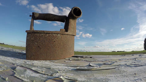historical rusty cloth iron on old table and clouds motion, time lapse 4K Filmmaterial