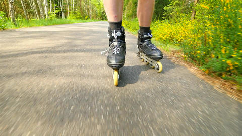 Outdoor inline skating on smooth asphalt in the forest. Close up view to light s Footage