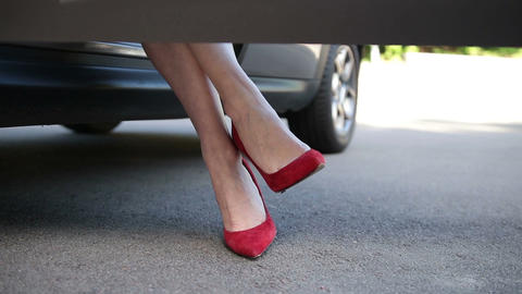 Woman in red high heels sitting in parked car Footage