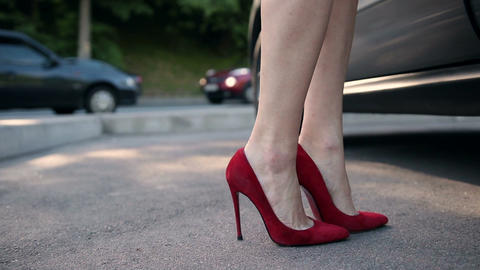 Woman wearing heels getting into parked car Footage
