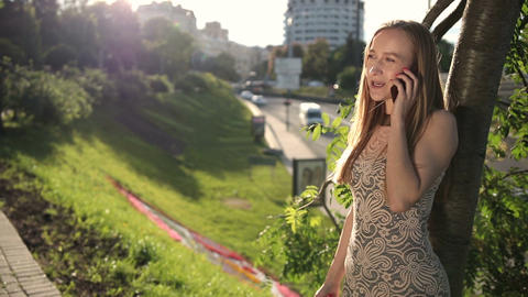Cheerful blonde woman talking on phone outdoors Footage