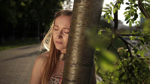 Despaired woman leaning her head on tree trunk Live Action