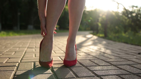 Woman in red high heels sprains foot on the street Footage
