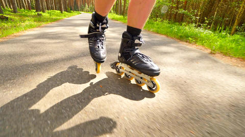Outdoor shuffle inline skating and t-braking. Mans legs roller skating on forest Footage
