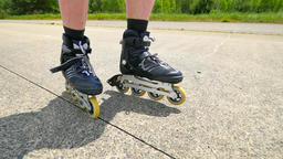Mans legs roller skating on the asphal. Close up view to quick movement of black Footage