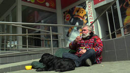 Senior man homeless in city begging and drinking alcohol Footage