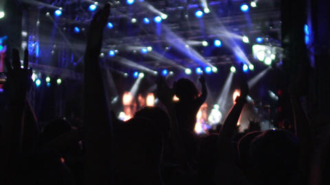 Silhouettes of fans waving hands in brightly illuminated concert hall, dancing Footage