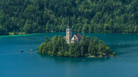 Island with church in middle of Lake Bled in Slovenia, boats coming and leaving Footage