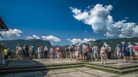 Tourists posing and taking pictures at observation site in mountains, time lapse Footage