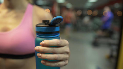 Sporty woman drinking water after finishing exercises in gym, close-up of bottle Footage