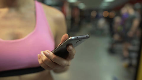 Woman scrolling pages on her mobile phone, having break from exercising in gym Live Action