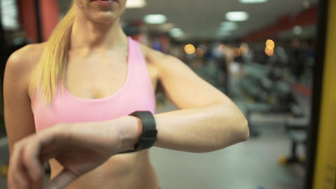 Female setting up smart watch before starting training in gym, fitness app Footage