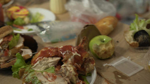Messy tables full of unhealthy food leftovers after student party in empty room Live Action