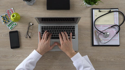 Medical worker typing on laptop, keeping electronic medical records, top view Live Action