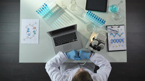 Scientist viewing samples under microscope and writing results on laptop in lab Footage