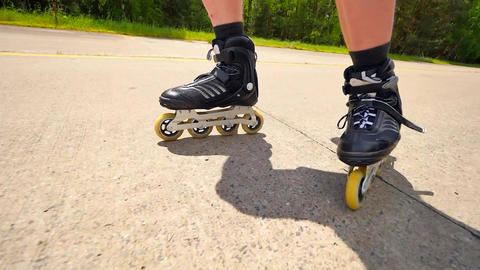 Very close up side view to working inline skates. Easy skating on the smooth asp Footage