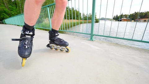 Front close view to inline skates riding on the bridge . Outdoor inline skating  Footage