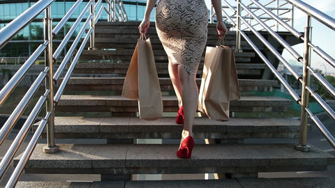 Woman legs walking on stairs with shopping bags Footage